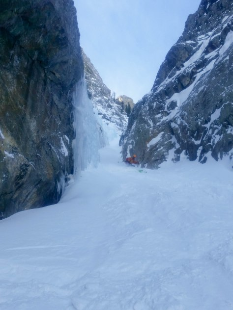 Tristen slashing the couloir powder as he exits the crux.