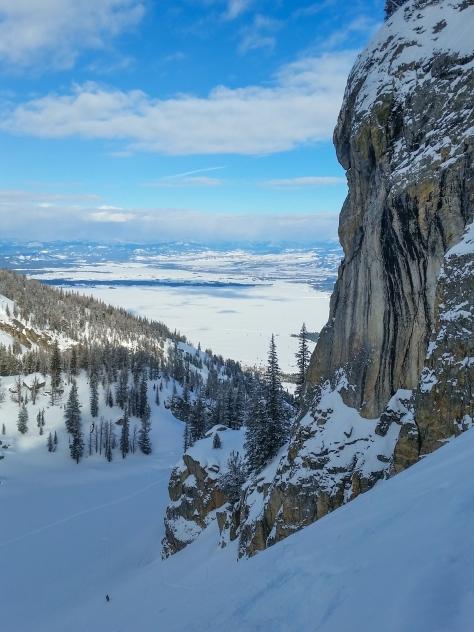 Little skier below a huge rock wall.